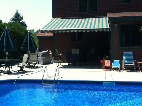 Blue and White patio awning providing shade near the pool