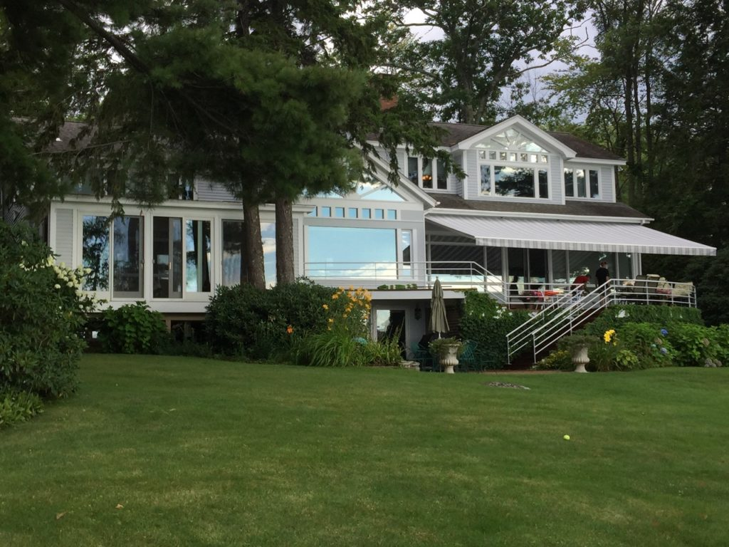 Lots of glass on this Lake Winnipesaukee waterfront Shielded by a large Sunesta awning