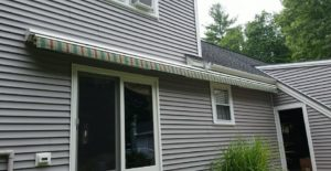 Sunesta retractable awning adds color to a gray house
