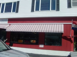 red and white commercial awning over a print business