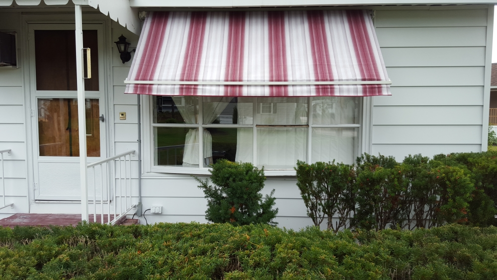 maroon and white retractable window awning