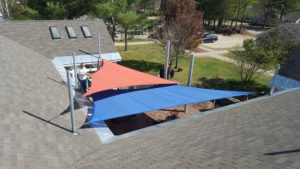 blue and orange sail awnings being installed