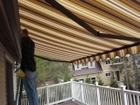 Up on a ladder repairing center ring on a roof mount awning