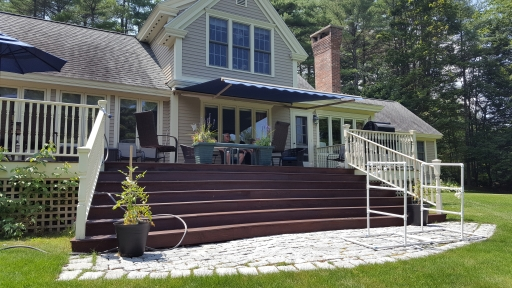 Sunesta retractable awning completes the outdoor living space at this peaceful lake home